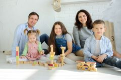 Day off in a big family. Dad, mom and three children are sitting on the floor. Younger children are built from tower cubes. Parents and the eldest daughter stock photography