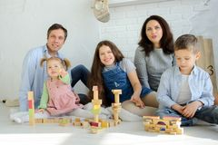 Day off in a big family. Dad, mom and three children are sitting on the floor. Younger children are built from tower cubes. Parents and the eldest daughter royalty free stock image