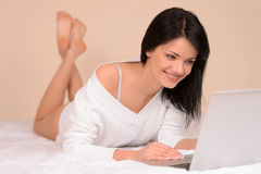 Day off at home. Beautiful young woman using computer while lyin Royalty Free Stock Photos