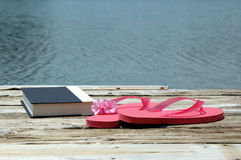 Day off at Lake. A book and sandals on a dock by the lake stock photography