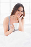Day off morning. Attractive young smiling woman sitting in bed and holding a cup while covered with blanket Royalty Free Stock Image