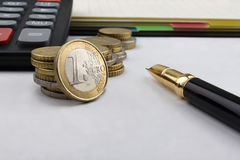 A day at the office. Euro (EUR) coins,notebook, a calculator and a pen, with a 1 EUR coin in front Royalty Free Stock Photography