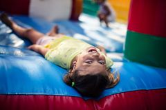 Day in the park can sometimes be difficult. Little girl lying on playground and looking at camera. Space for copy royalty free stock images