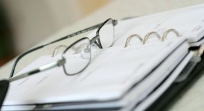 Day planner V. Dap planner with glasses. Shallow focus on glasses royalty free stock images