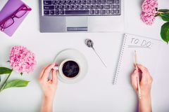Day Planning - female hands with cup of coffee and pencil write To do list on the white working office desk with laptop, notebook,. Glasses, and wisteria royalty free stock image