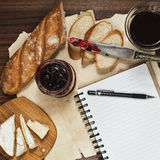 Day planning during the refined brunch meal. Refined meal with red wine, brie cheese and fresh bread with cranberry jam and a notebook for day planning royalty free stock photography