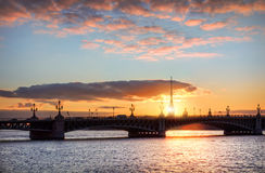 Day quickly slips. Sunset with beautiful pink clouds over the bridge across the Neva River and Peter and Paul Fortress Royalty Free Stock Photography