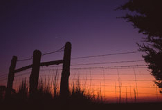 Day's End on the Farm. Silhoutte of fence posts and wire fence at dusk stock photos