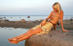 Day at the seashore. Lovely girl relaxing on the rock Royalty Free Stock Photos