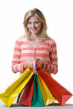 After a day of shopping. Attractive blond woman holding onto a bunch of colorful shopping bags