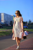 After day shopping. Close-up of young woman carrying shopping bags while walking along the street. stock photo