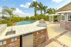 Day shot of a wonder California home with a large pool and count. Er space for a barbecue on a bright sunny day with puffy clouds. Wonderful California home in Stock Photography