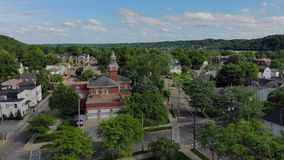 Day slow wide forward aerial establishing shot of small town hall Steeple. A slow moving forward wide aerial establishing shot of the steeple of a city hall in stock video footage
