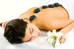 The day spa. Portrait of young woman at the day spa with black stones on her bare back Stock Photo