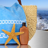 Day Spa, Beach Bag With Starfish Sunscreen. Day Spa Still-life Beach Bag With Starfish And Sunscreen On Metal Table With Ocean Waves In Background Stock Photography