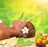 Day spa. Beautiful young african woman enjoying day spa, lying down on massage table with closed eyes, take medical treatment outdoors, luxury spa resort Stock Image