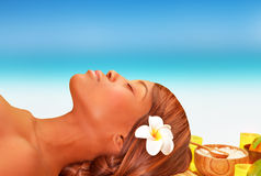 Day spa. Closeup portrait of attractive African woman lying down on massage table on the beach in luxury spa resort, summer vacation concept Stock Photo