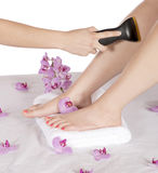 Day spa hair removal by masseuse on leg Stock Image