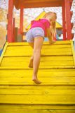Day is sunny and created for the play. Little girl climbing and playing in playground. Close up. Space for copy stock image