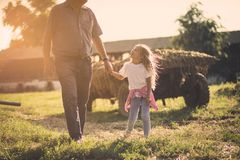 Day for talk and walk. Grandfather and granddaughter walking together in the backyard royalty free stock image