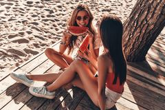 Day time fun. Top view of two attractive young women smiling and eating watermelon while sitting on the beach stock images
