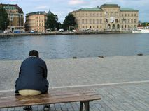 Day time rest. Man sitting on Stockholm embankment Stock Photos