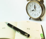 Day timer organizer with a pen and a mechanical alarm clock, time management and activity planning concept Stock Photography