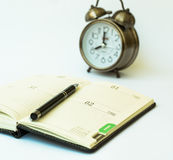 Day timer organizer with a pen and a mechanical alarm clock, time management and activity planning concept Stock Photos