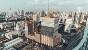 Day to night holy grail time-lapse of building construction site in city, end with traffic light trails and rain, aerial view stock video footage