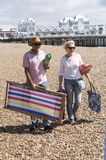 Day trippers on the beach in Southsea southern England. Elderly couple walking with a deckchair on a shingle beach. Southsea, England UK Stock Image