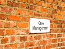 Day view Care Management banner label on red brick wall in UK.  Stock Photos