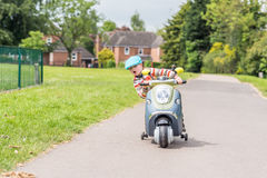 Day view child boy riding scooter summer park Royalty Free Stock Image
