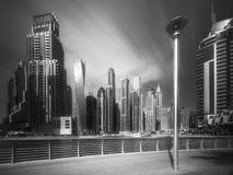 Day view of Dubai Marina bay with cloudy sky, UAE. Modern buildings of Dubai Marina bay with cloudy sky during sunny day, UAE. Black and white concept Stock Image