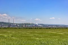 Day view of a industrial valley. Day view of a factory in the middle of a green rice field. Factory pipes polluting air on a silent stock images