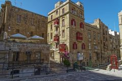 Valletta, Malta Traditional buildings with red balconies. Day view of Maltese limestone buildings with British phone booth in the streets of the capital of Stock Photo