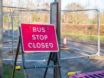 Day view sign informing about roadworks next to bus stop on UK road.  Stock Images