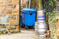 Day view of stacked beer casks of kegs at the back of the pub with recycly bin and shopping trolley next to it.  Stock Photography