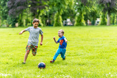 Day view of two boys playing football summer park Royalty Free Stock Image
