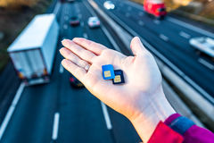 Day view of woman hand holding sim cards over UK Motorway. Royalty Free Stock Image