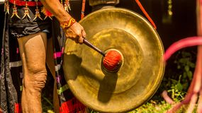 Dayak male hit the gong. At traditional ceremony Stock Photos