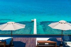Daybed op het strand met blauwe overzees Stock Afbeeldingen