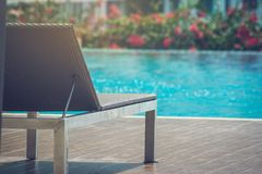 Daybed place on wooden terrace nearly blue water of swimming pool. royalty free stock photography
