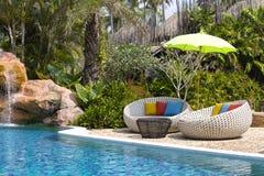 Daybeds de piscine et de rotin dans un jardin tropical, Thaïlande images libres de droits