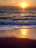 Daybreak in Palm Beach, Florida. Reflections of a rising Florida sun over the waves and wet shoreline Stock Photo