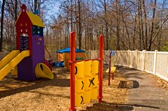 Daycare playground equipment. Colorful children's playground equipment at a daycare center with a variety of toys, including a slide and tic-tac-toe game to play Stock Photo