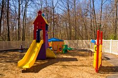 Daycare playground equipment. Colorful children's playground equipment at a daycare center with a variety of toys, including a slide and games to play on during Stock Photos