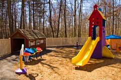 Daycare playground equipment. Colorful children's playground equipment at a daycare center with a variety of toys, including a slide and little house to play on Royalty Free Stock Images