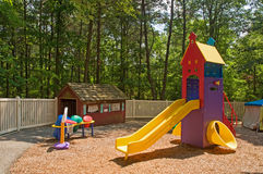 Daycare playground equipment. Colorful children's playground equipment at a daycare center with a variety of toys, including a slide and little house to play on Royalty Free Stock Photography
