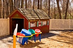 Daycare playhouse and toys. Colorful children's playground equipment at a daycare center with a variety of toys a little play house on and basketball hoop on a Stock Image
