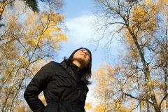 Daydream. Elegant dark-haired girl dreams in autumn park looking on a serene sky Stock Photos